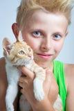 Boy hugging ginger kitten stock images