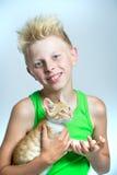 Boy hugging ginger kitten royalty free stock photos