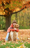 Boy Hugging Golden Retriever. Boy Giving Golden Retriever a Hug under a Beautiful Fall Tree royalty free stock images