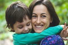 The boy is hugging his mother. Mom`s embrace. The boy is hugging his mother. Smiling women walks with her son in nature. Portrait of a women with a child. Time stock photo