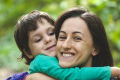The boy is hugging his mother. Mom`s embrace. The boy is hugging his mother. Smiling women walks with her son in nature. Portrait of a women with a child. Time royalty free stock image