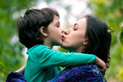 The boy is hugging his mother. Mom`s embrace. The boy is hugging his mother. Smiling women walks with her son in nature. Portrait of a women with a child. Time stock photography