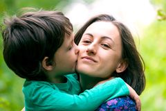 The boy is hugging his mother. Mom`s embrace. The boy is hugging his mother. Smiling women walks with her son in nature. Portrait of a women with a child. Time royalty free stock images