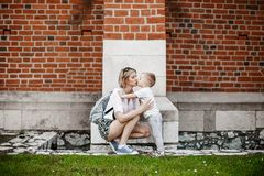 The boy is hugging his mother. The son kisses his mother. Outdoor walk Stock Photos