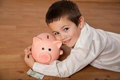 Boy hugging his piggy bank Royalty Free Stock Image