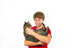 Boy hugging his tabby cat Stock Image