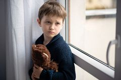 Boy is hugging his teddy bear. Standing by the window. royalty free stock image