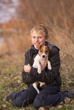 Boy hugging a Jack Russell puppy Stock Image