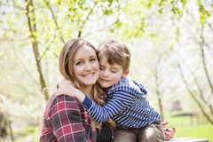 Boy hugging mother outside in spring Stock Photo