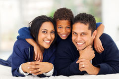 Boy hugging parents. Little indian boy hugging his parents while lying on bed Stock Photography