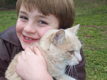 Boy hugging pet cat Royalty Free Stock Images