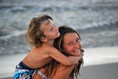 Boy hugging sister while on her back. A toddler boy on his sister's back and hugging her while she is smiling and they are on the beach with the ocean and waves Stock Photos