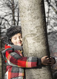 Boy hugging a tree, listening the sounds of the Nature. Stock Image