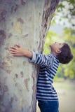 Boy hugging tree trunk in park. Smiling boy hugging tree trunk in park Stock Photo