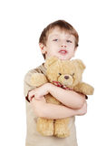 Boy hugs bear-toy and says something. Stock Photos