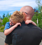 Boy hugs father. Young boy jumps into his fathers arms with a big hug for joy royalty free stock photo