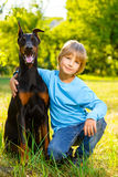 Boy hugs his beloved dog or doberman in summer Stock Images