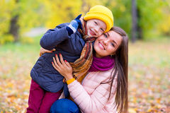 Boy hugs his mother in autumn park Royalty Free Stock Photography