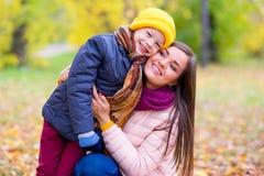 Boy hugs his mother in autumn park Royalty Free Stock Photos