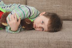 Boy hugs his teddy bear and lying on the sofa royalty free stock image