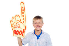 Boy with a hurray boo foam hand. Young fan. Handsome boy with a hurray boo foam hand pointing skywards on isolated white background Royalty Free Stock Photo
