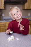 Boy icing cookie Stock Images
