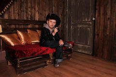 Boy in the image of a cowboy. Boy in a black leather jacket and a cowboy hat Royalty Free Stock Image