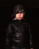 Boy in the image of a gangster rapper. Kid in leather jacket, baseball cap over a black background Stock Image