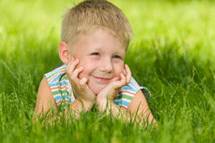 Boy imagines on the green grass Stock Image