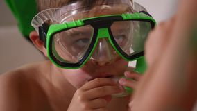 The boy imitates swimming on the couch, and the girl blows bubbles on him, close up.  Royalty Free Stock Images