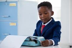 Boy imitating as businessman working on typewriter Stock Photography