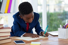 Boy imitating as businessman writing on diary. At desk in office Stock Photo