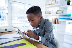 Boy imiting as businessman writing on paper attached to clipboard. While sitting at desk in office Stock Photo