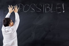 Boy with Impossible word on chalkboard Stock Images