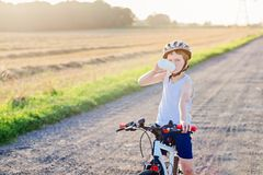 Free Boy In A Bicycle Helmet Drinks Bottled Water Stock Photography - 97208982