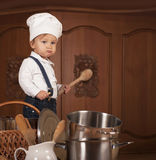 Boy In A Cook Cap Among Pans And Vegetables Stock Images