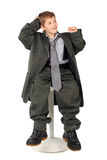 Boy In Big Man S Suit Sitting On Chair Isolated Royalty Free Stock Images