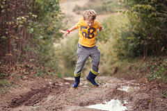 Boy In Gumboots Jumps Into The Puddle Royalty Free Stock Image