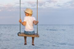 Free Boy In Straw Hat Sitting On A Rope Swing On Sea Background. Back View Royalty Free Stock Photography - 209002217