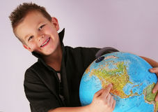 Boy is indicating america. Boy is holding the world and america in his hands Stock Photography