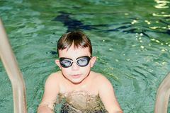 Boy in the indoor public pool. Portrait of child with swimmng goggles. Boy goes up on ladder. Royalty Free Stock Photos