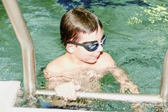 Boy in the indoor public pool. Portrait of child with swimmng goggles. Boy goes up on ladder. Royalty Free Stock Image