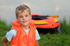 Boy and inflatable boat ashore. Summer royalty free stock photography