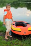 Boy and inflatable boat ashore Royalty Free Stock Image