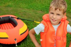 Boy and inflatable boat on lawn. Summer stock photos