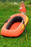Boy and inflatable boat on lawn. Summer stock image