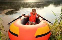 Boy in inflatable boat in water. Summer stock photo