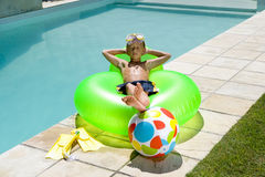 Boy (9-11) on inflatable chair by swimming pool, arms behind head Royalty Free Stock Images