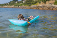Boy  on inflatable mattrass Stock Photography
