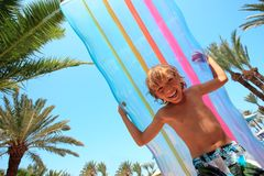 Boy with inflatable mattress. Boy carrying a large inflatable mattress or float at a tropical resort stock images